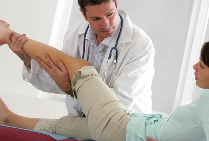 Доктор проводит осмотр ноги