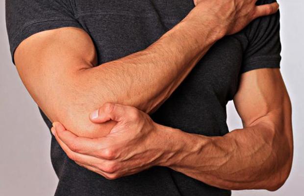 У мужчины болят локти после тренировки